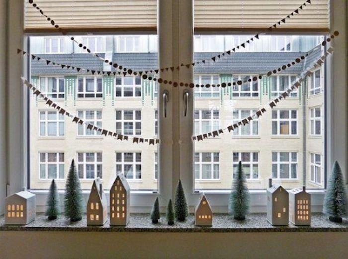 Mô hình ngôi nhà bìa carton nhỏ xinh đặt cạnh cửa kính dịp Noel